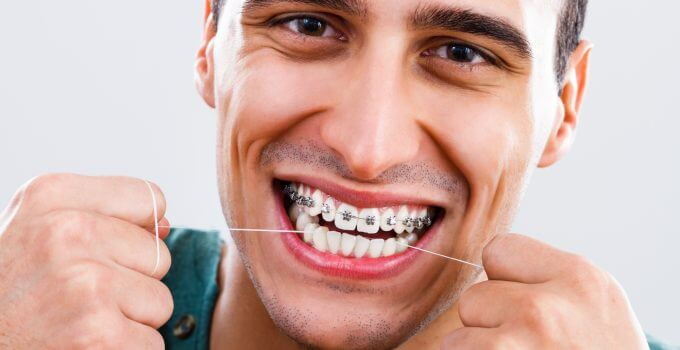 man flossing with braces