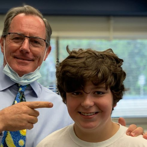dr-john-pointing-to-teen-patient-boy