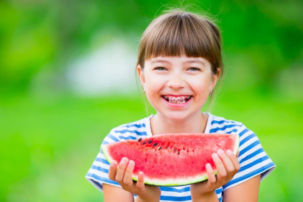 girl with braces holding a slice of watermelon