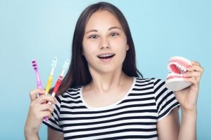 teen girl with braces holding a fake mouth and toothbrushes