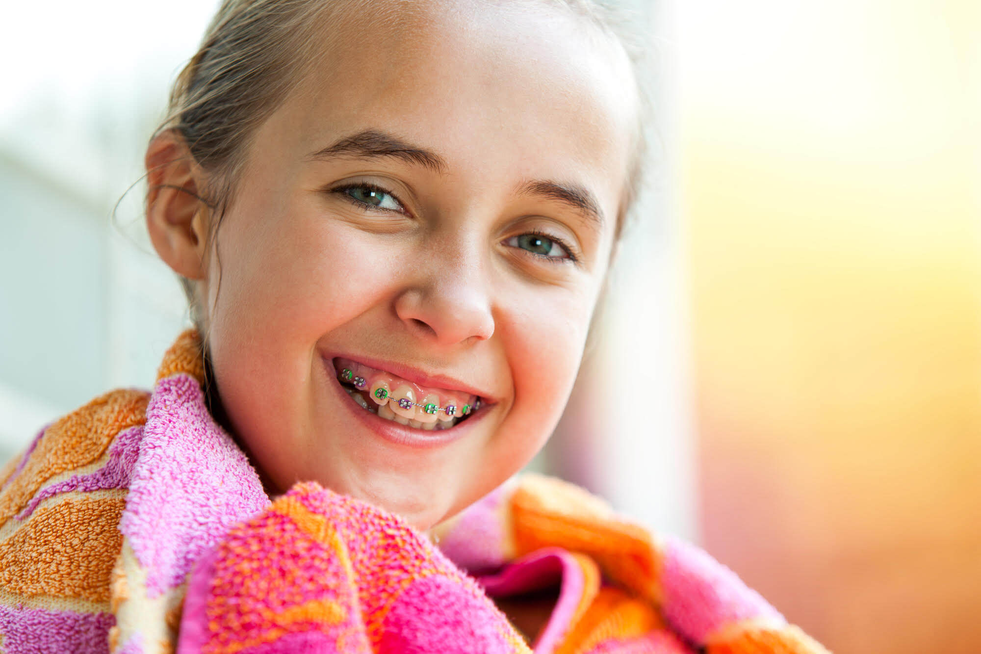 cute girl smiling with braces while wrapped up in a towel after swimming