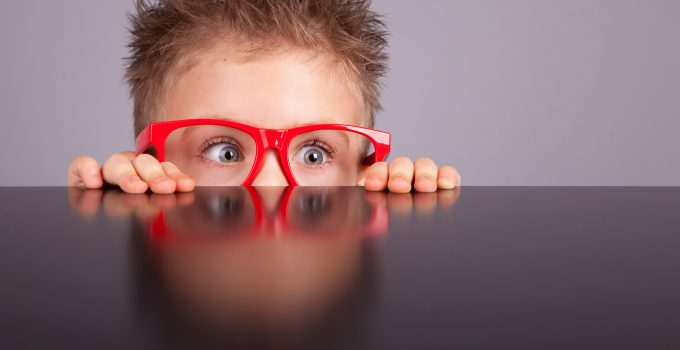 nervous little boy with red glasses hiding behind table